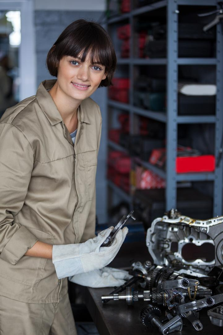 Portrait of female mechanic working on an car parts