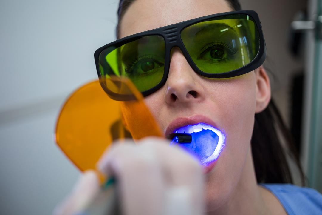 Dentist examining patients teeth with dental curing light at clinic