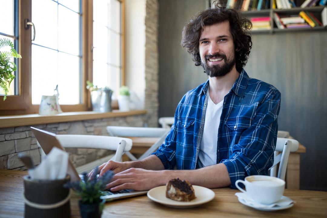 Portrait of smiling man using laptop in coffee shop