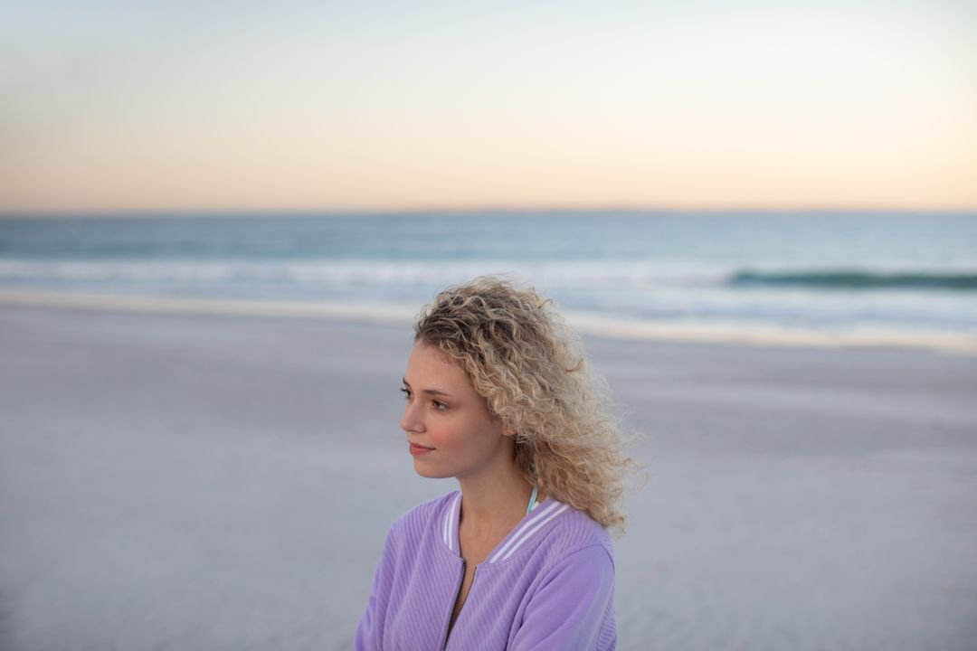 Thoughtful beautiful woman standing on the beach
