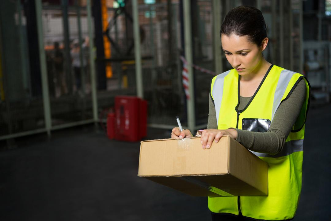 Confident female worker writing on box in warehouse