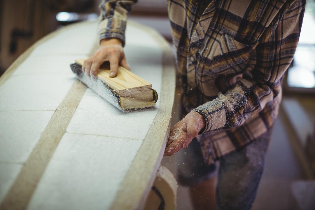 Mid-section of man using sanding block in the surfboard workshop