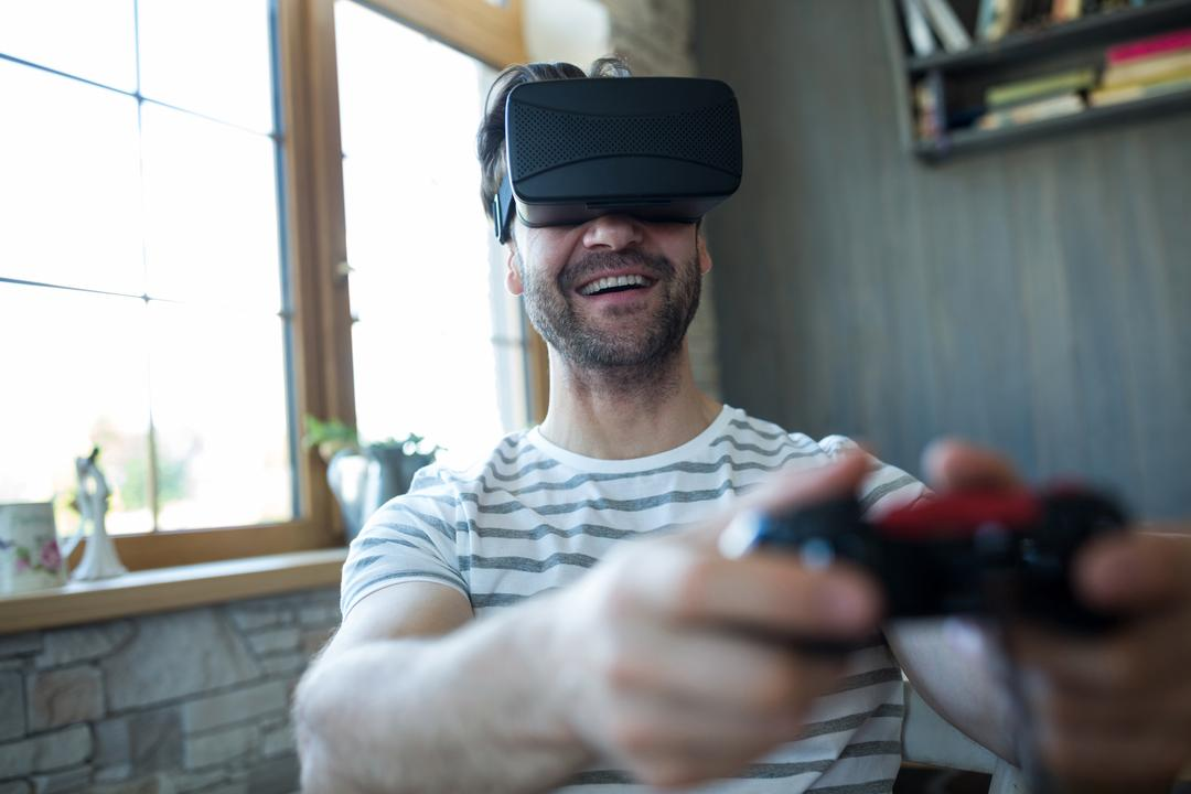 Happy man using virtual reality headset and playing video game at coffee shop Free Stock Images from PikWizard