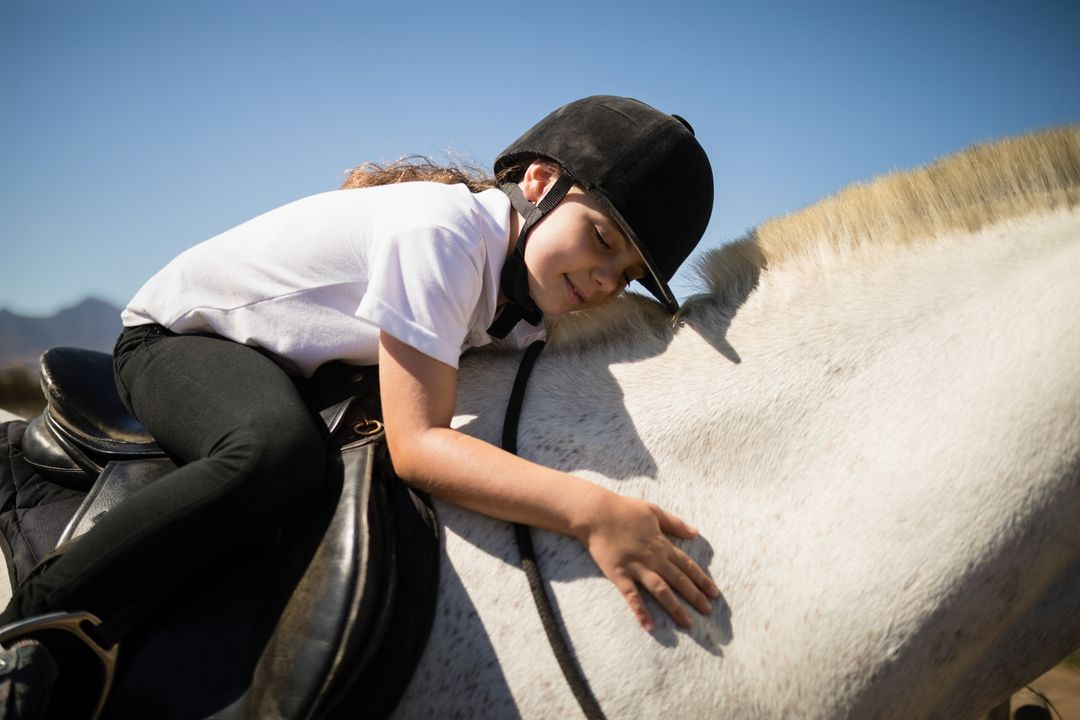 Smiling girl embracing the white horse in the ranch on a sunny day