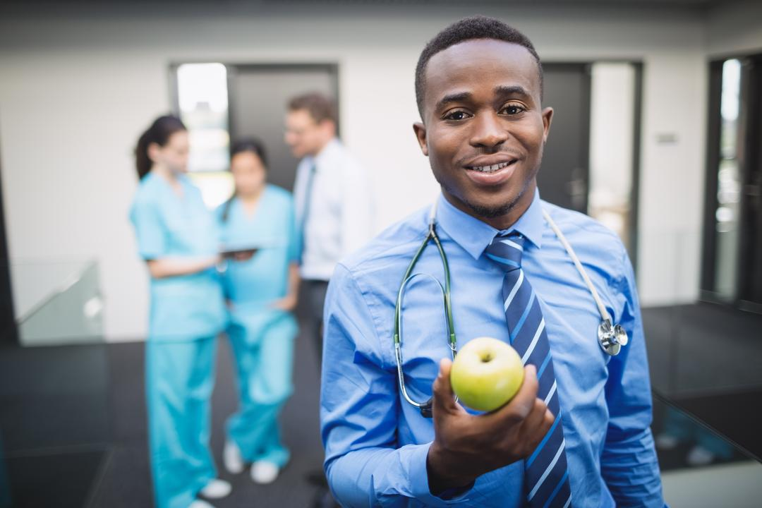 Portrait of smiling doctor holding green apple in hospital corridor