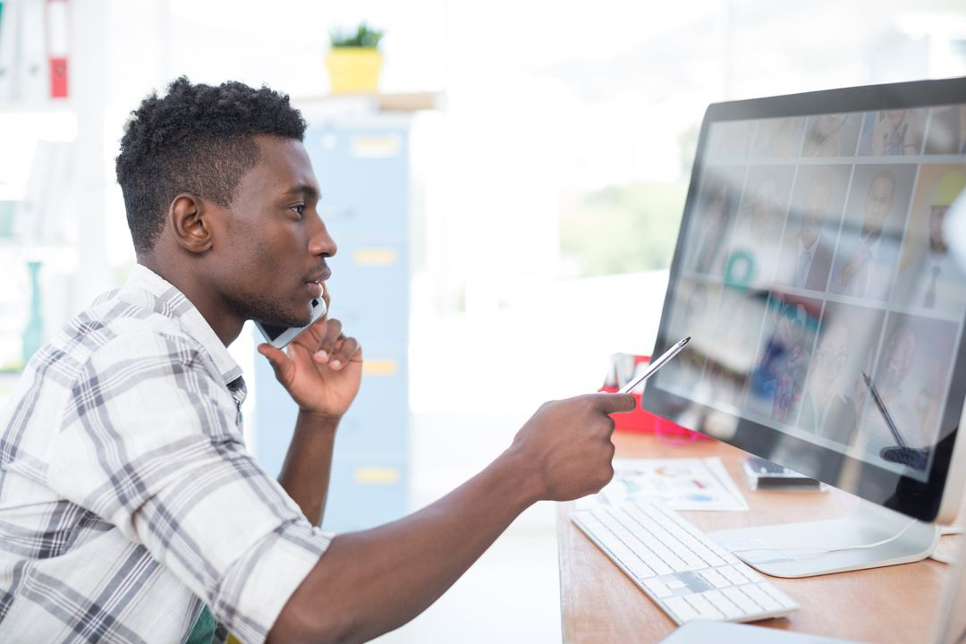 Male worker pointing his pen at the computer screen while answering a call