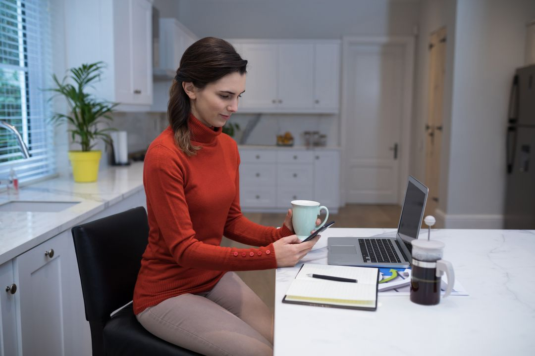 Woman using mobile phone while having coffee at desk Free Stock Images from PikWizard
