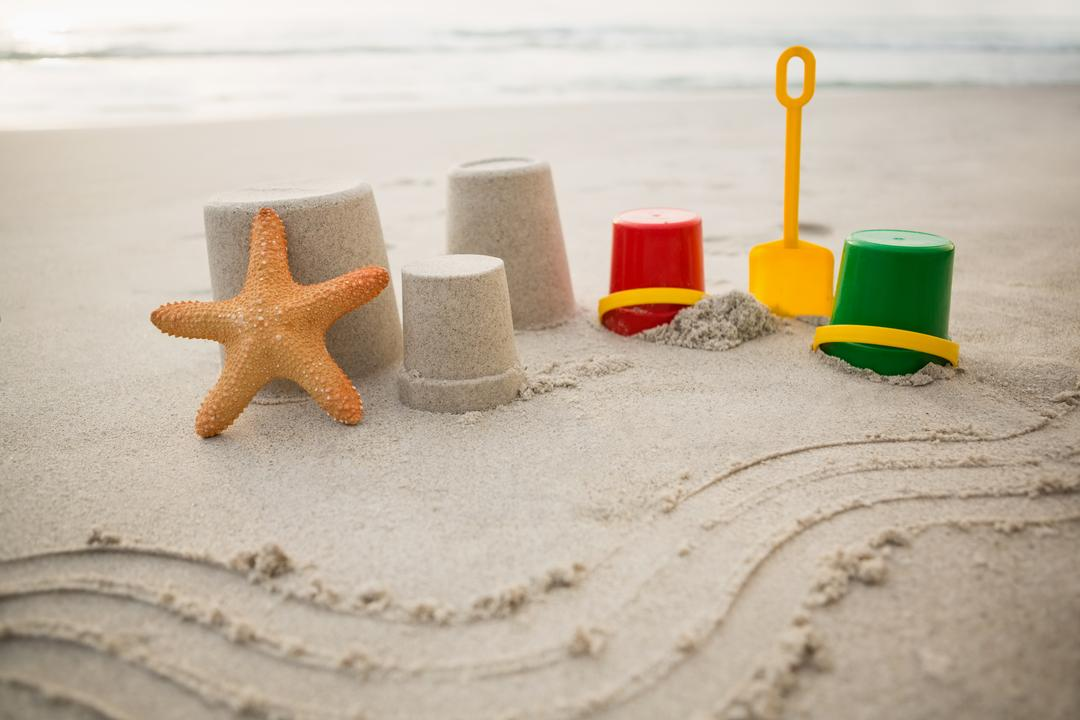 Bucket, spade, starfish and sand castles on tropical sand beach Free Stock Images from PikWizard