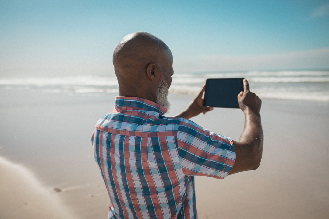 Man standing on a beach taking photographs