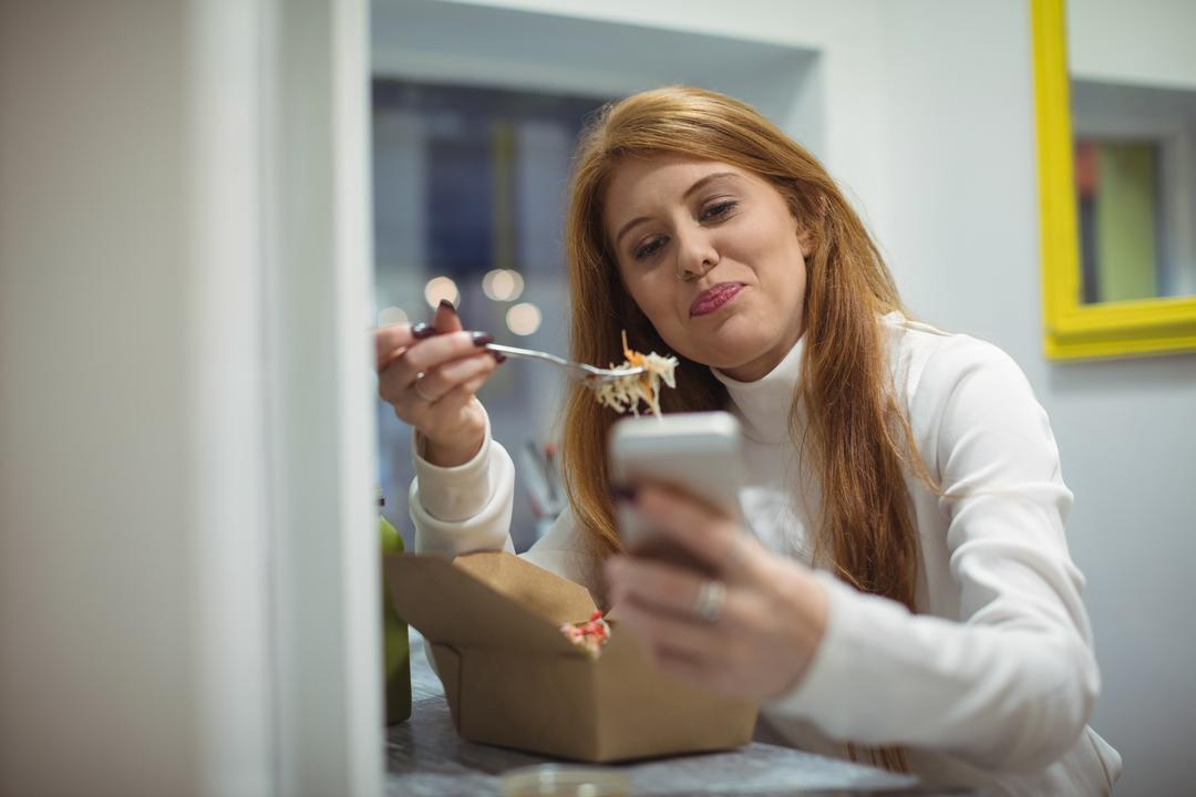 Beautiful woman using mobile phone while eating salad. Young redhead enjoying a beautiful sunny autumns day