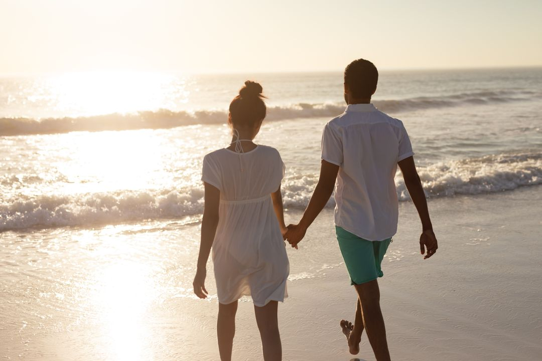 Rear view of couple walking together hand in hand on the beach