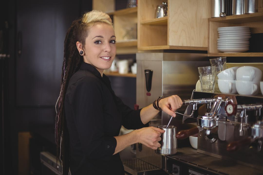 Portrait of smiling waitress using the coffee machine in cafe