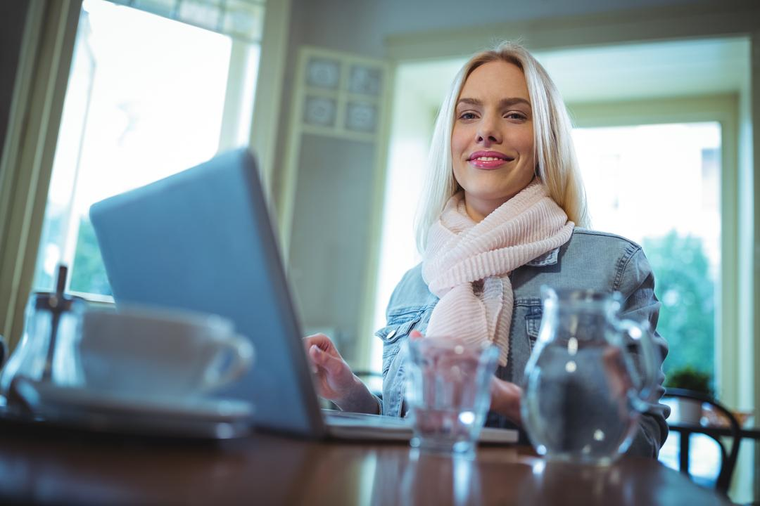 Portrait of smiling woman using laptop while having coffee in café