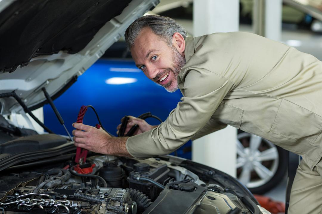 Mechanic attaching jumper cables to car battery in repair garage