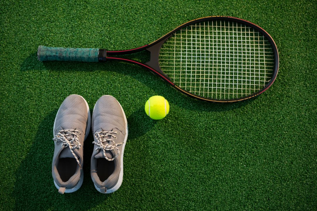 Overhead view of racket with tennis ball and sports shoes on field Free Stock Images from PikWizard