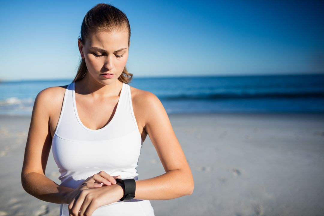 Woman using a smart watch on the beach Free Stock Images from PikWizard