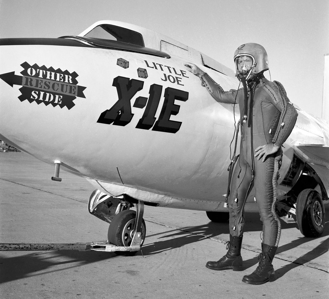 "Joe Walker in a pressure suit beside the X-1E at the NASA High-Speed Flight Station, Edwards,California. The dice and ""Little Joe"" are prominently displayed under the cockpit area. (Little Joe is a dice players slang term for two deuces.) Walker is shown in the photo wearing an early Air Force partial pressure suit. This protected the pilot if cockpit pressure was lost above 50,000 feet. Similar suits were used in such aircraft as B-47s, B-52s, F-104s, U-2s, and the X-2 and D-558-II research aircraft. Five years later, Walker reached 354,200 feet in the X-15. Similar artwork - reading ""Little Joe the II"" - was applied for the record flight. These cases are two of the few times that research aircraft carried such nose art."