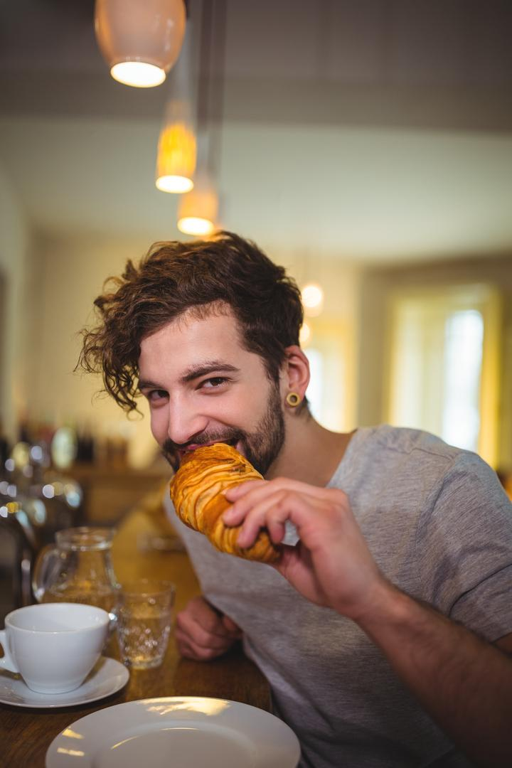 Portrait of man eating a croissant in café