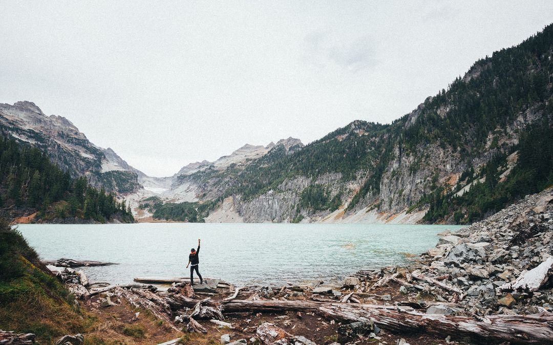 Man standing at lake with mountain range in background