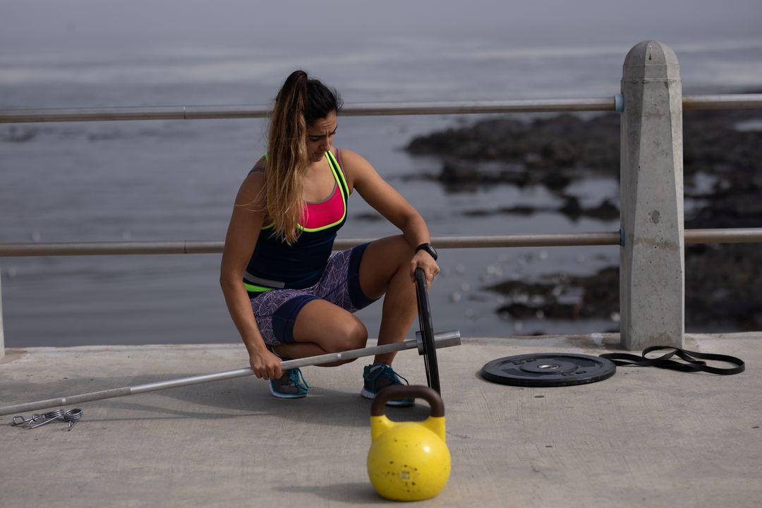 Strong woman preparing barbells to exercising outdoors by the seaside