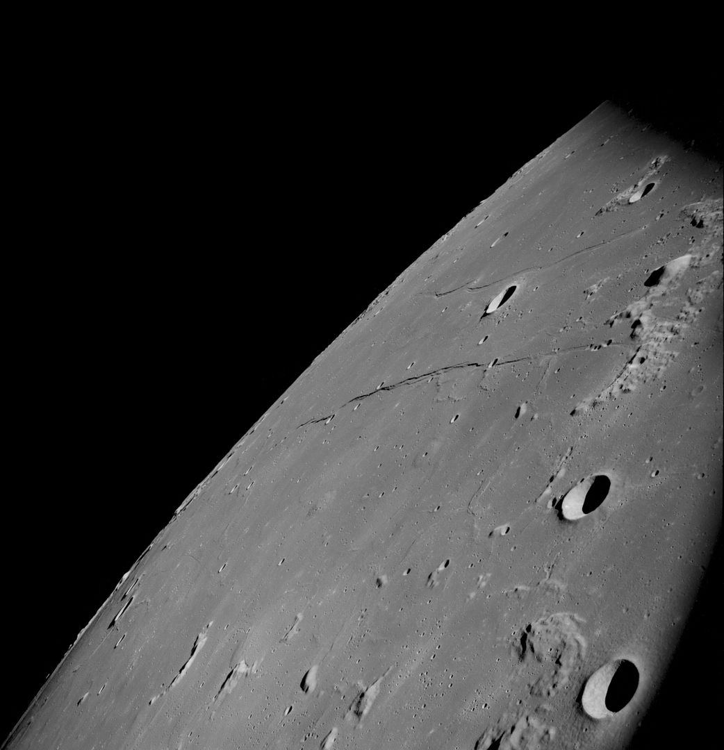 AS08-13-2344 (21-27 Dec. 1968) --- This oblique photograph looks generally northwest from the Apollo 8 spacecraft into the Sea of Tranquility. (HOLD PICTURE WITH LARGE TRIANGLE FORMED BY DARK SKY AT UPPER LEFT). The three prominent craters are Taruntius F in the lower right corner; Taruntius E in the center; and Cauchy between the two linear features. The Cauchy scarp, this side of the Cauchy crater, is formed by one to three faults stepped down toward the spacecraft. Cauchy Rille, on the other side of Cauchy crater, consists of several arcuate segments of a graben. Each of the three prominent craters is 10 to 15 kilometers (6 to 9 statute miles) across.