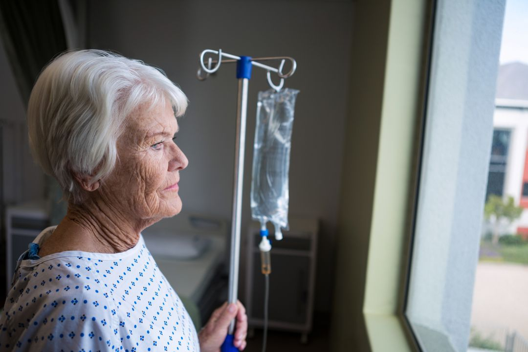 Thoughtful senior patient standing at hospital Free Stock Images from PikWizard