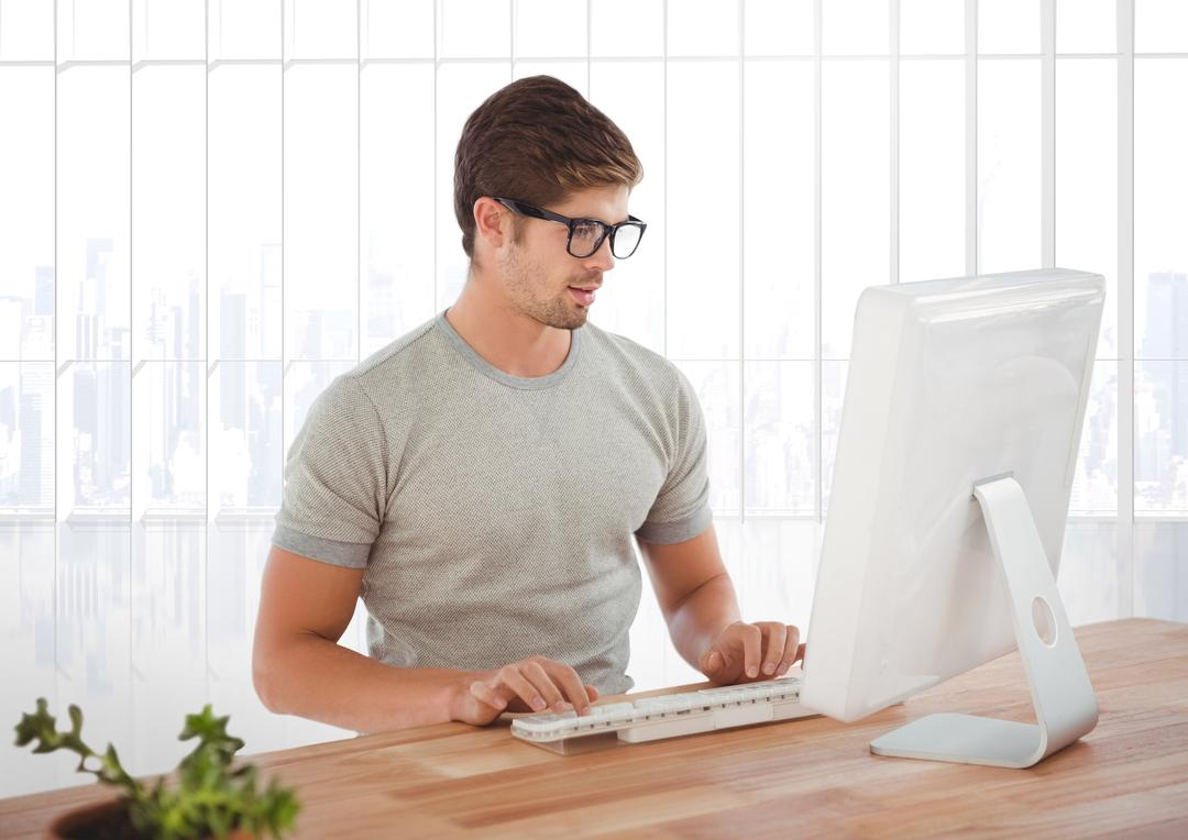 Handsome man in spectacles using desktop pc