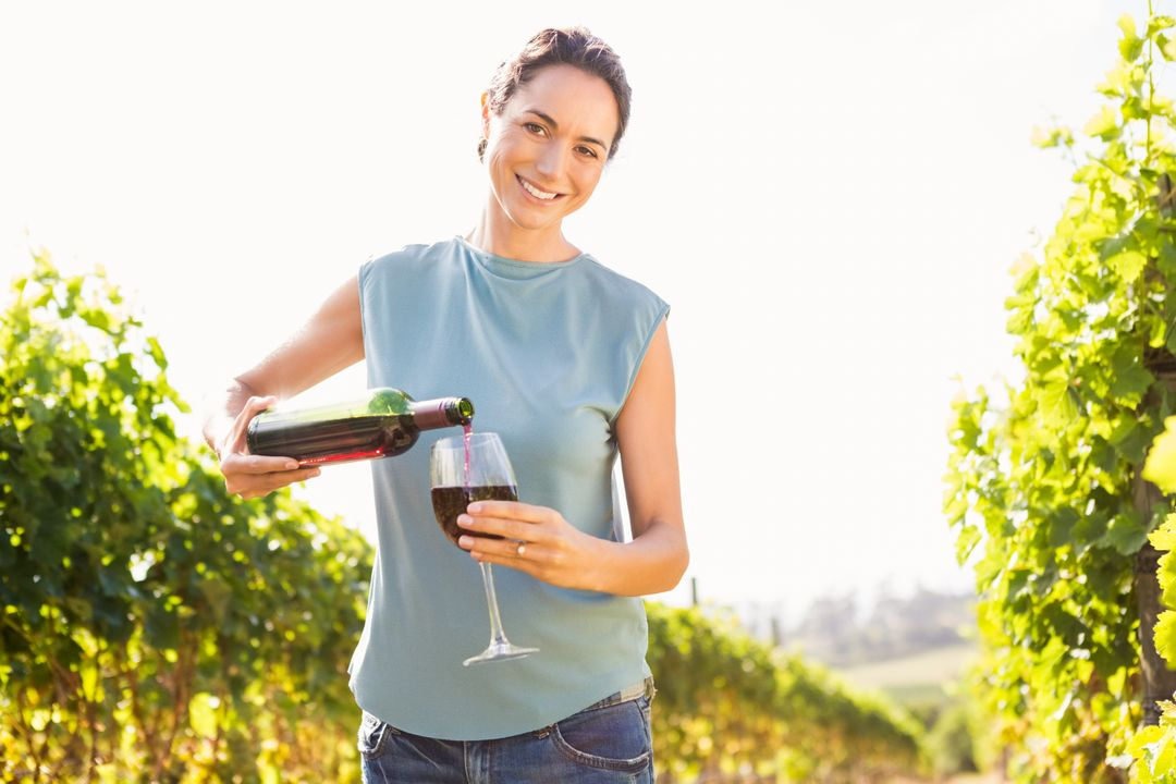 Portrait of smiling woman pouring red wine from bottle in glass at vineyard on sunny day Free Stock Images from PikWizard