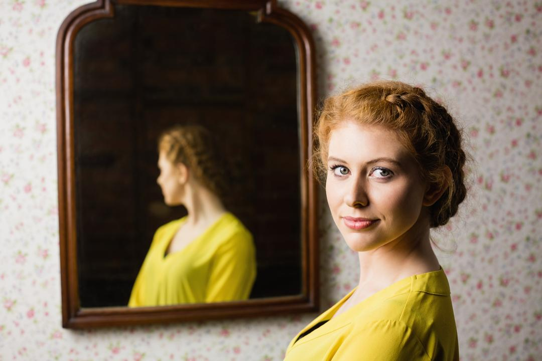 Portrait of a beautiful woman standing in front of mirror