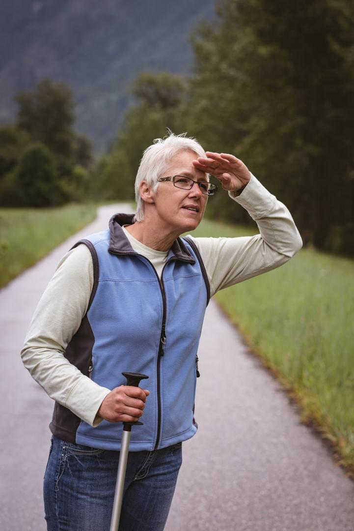 Senior woman hiker looking at a distance in the forest