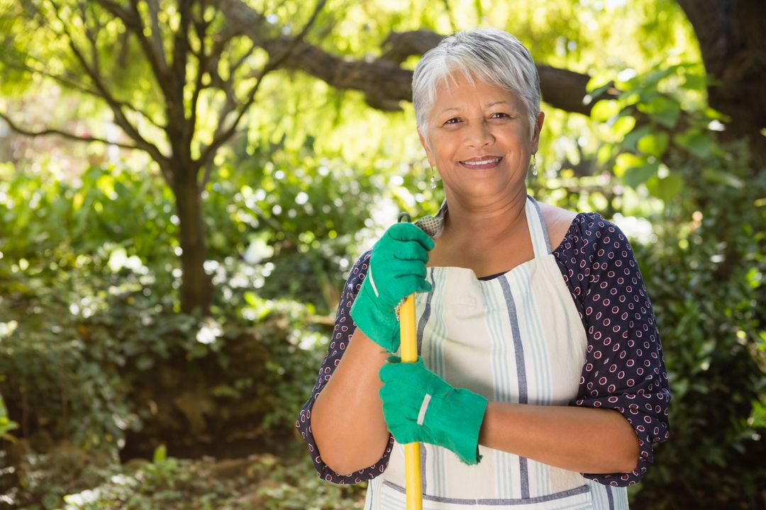 Portrait of senior woman standing in garden on a sunny day Free Stock Images from PikWizard