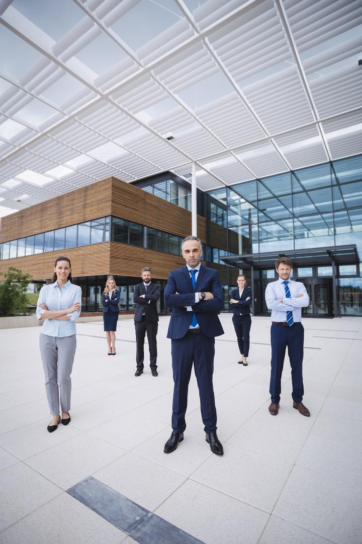 Group of confident businesspeople standing with arms crossed outside office building