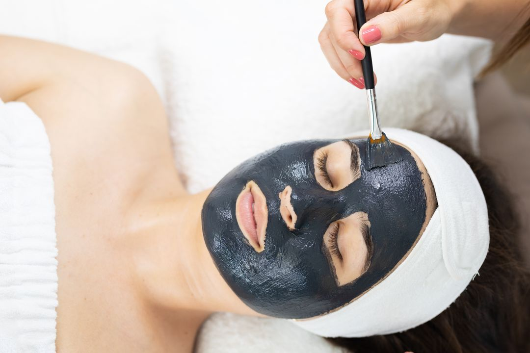 Woman with face mask applied by beautician