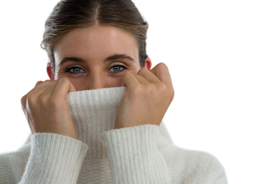 Portrait of woman covering face with turtleneck sweater against white background Free Stock Images from PikWizard