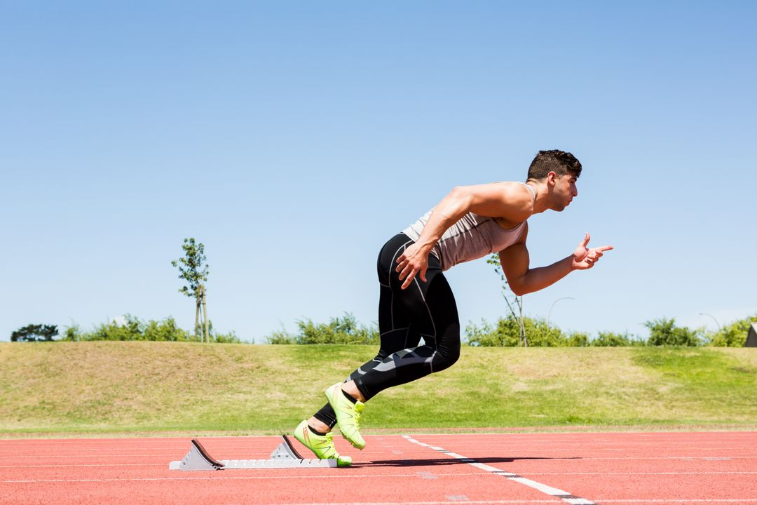 Man running on a track field on a sunny day