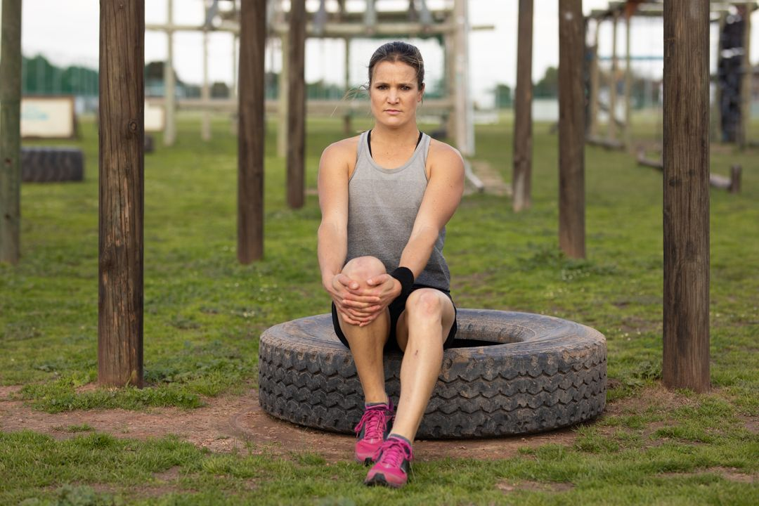 Portrait of woman sitting on a tyre before bootcamp training session