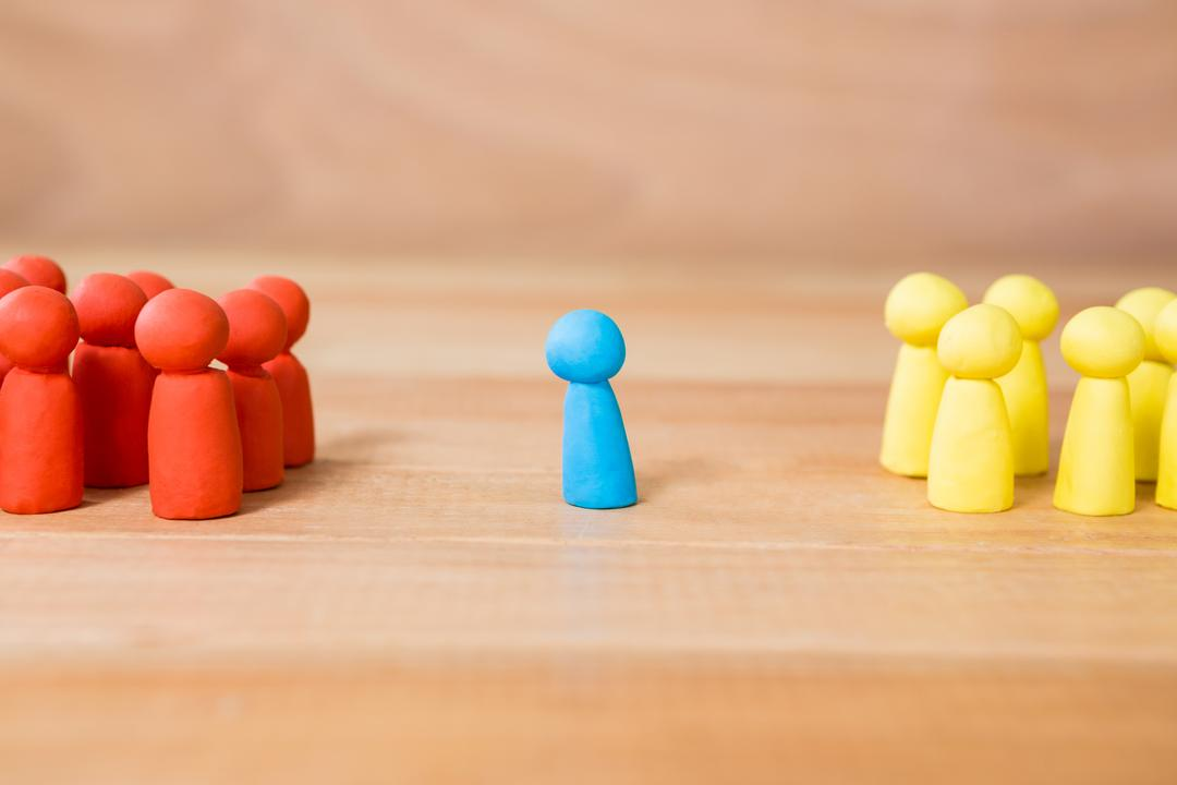 Conceptual image of blue figurine standing between a group of red and yellow figurines