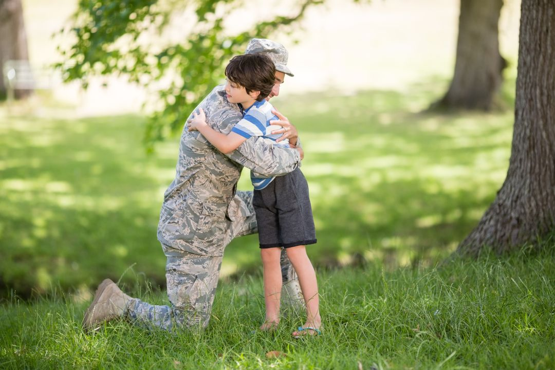 Army soldier embracing boy in park on a sunny day Free Stock Images from PikWizard