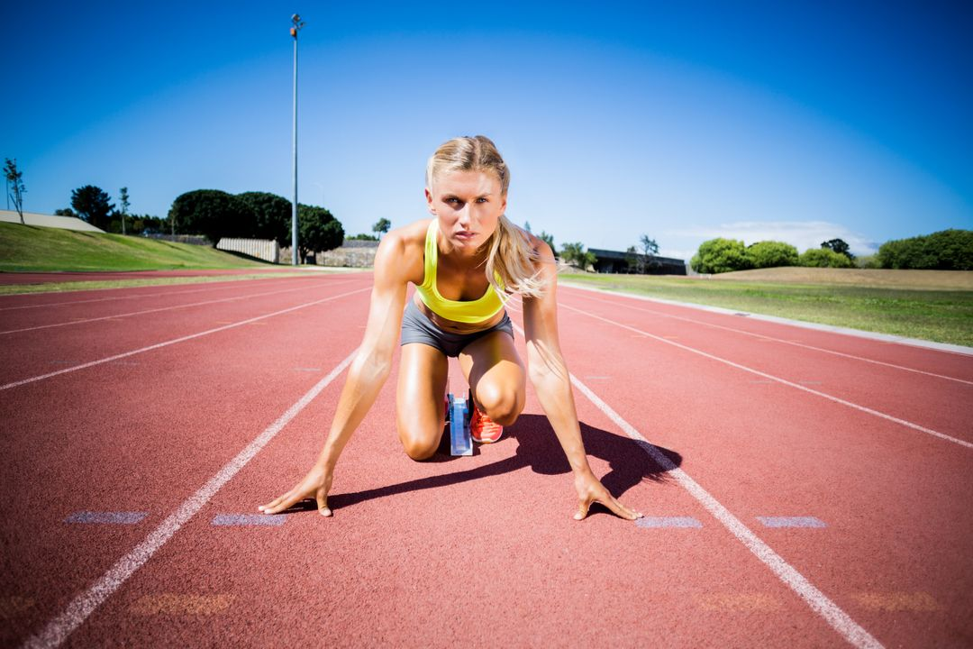 Female athlete ready to run on running track on a sunny day Free Stock Images from PikWizard