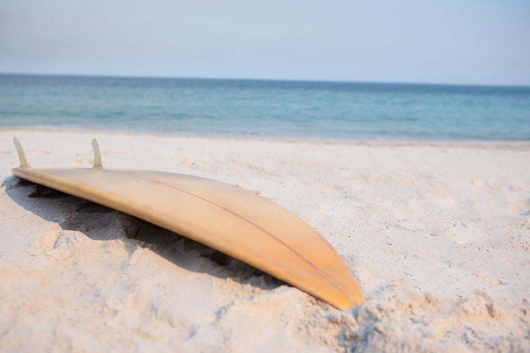 Wooden surfboard on sand at beach during sunny day