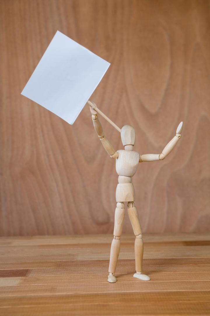 Conceptual image of figurine holding a signboard Free Stock Images from PikWizard