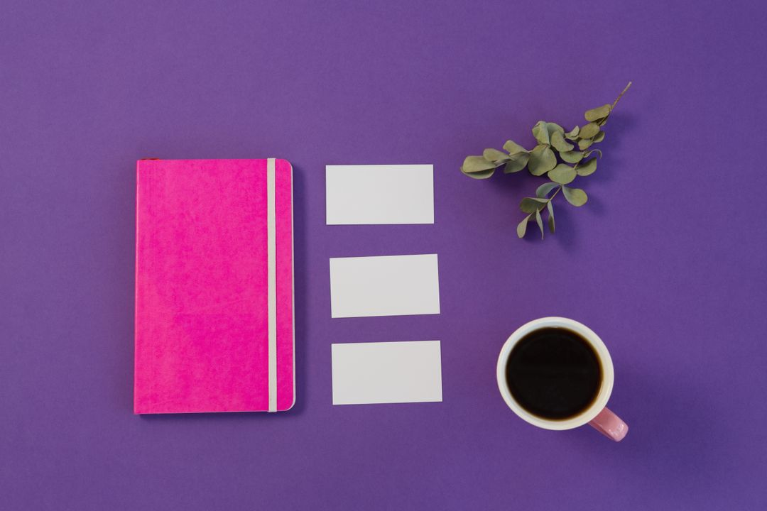 Aesthetic image of purple background with pink notebook, dried leaves, coffee and small white cards