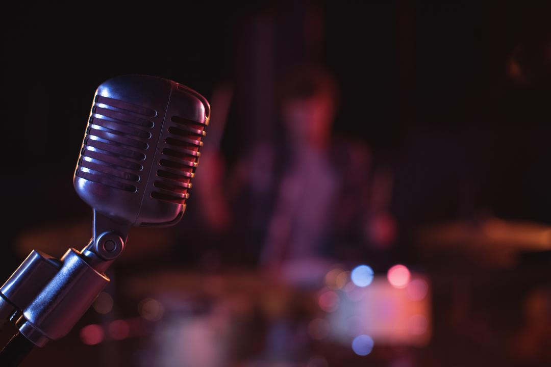Close-up of retro microphone against band background in recording studio