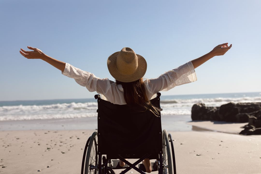 Rear view of disabled woman with arms outstretched on the beach