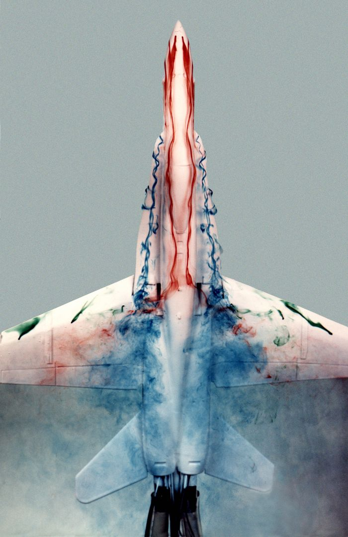"This image shows a plastic 1/48-scale model of an F-18 aircraft inside the ""Water Tunnel"" more formally known as the NASA Dryden Flow Visualization Facility. Water is pumped through the tunnel in the direction of normal airflow over the aircraft; then, colored dyes are pumped through tubes with needle valves. The dyes flow back along the airframe and over the airfoils highlighting their aerodynamic characteristics. The aircraft can also be moved through its pitch axis to observe airflow disruptions while simulating actual flight at high angles of attack. The Water Tunnel at NASA's Dryden Flight Research Center, Edwards, CA, became operational in 1983 when Dryden was a Flight Research Facility under the management of the Ames Research Center in Mountain View, CA. As a medium for visualizing fluid flow, water has played a significant role. Its use dates back to Leonardo da Vinci (1452-1519), the Renaissance Italian engineer, architect, painter, and sculptor. In more recent times, water tunnels have assisted the study of complex flows and flow-field interactions on aircraft shapes that generate strong vortex flows. Flow visualization in water tunnels assists in determining the strength of vortices, their location, and possible methods of controlling them.  The design of the Dryden Water Tunnel imitated that of the Northrop Corporation's tunnel in Hawthorne, CA. Called the Flow Visualization Facility, the Dryden tunnel was built to assist researchers in understanding the aerodynamics of aircraft configured in such a way that they create strong vortex flows, particularly at high angles of attack. The tunnel provides results that compare well with data from aircraft in actual flight in another fluid-air. Other uses of the tunnel have included study of how such flight hardware as antennas, probes, pylons, parachutes, and experimental fixtures affect airflow. The facility has also been helpful in finding the best locations for emitting smoke from flight vehicles for flow vi"