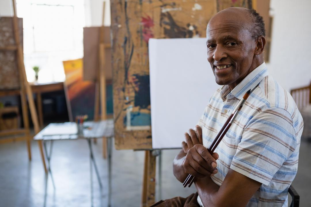 Portrait of smiling senior man with arms crossed sitting by easel in art class Free Stock Images from PikWizard