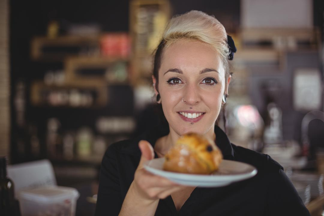 Portrait of waitress holding plate with muffin in cafe
