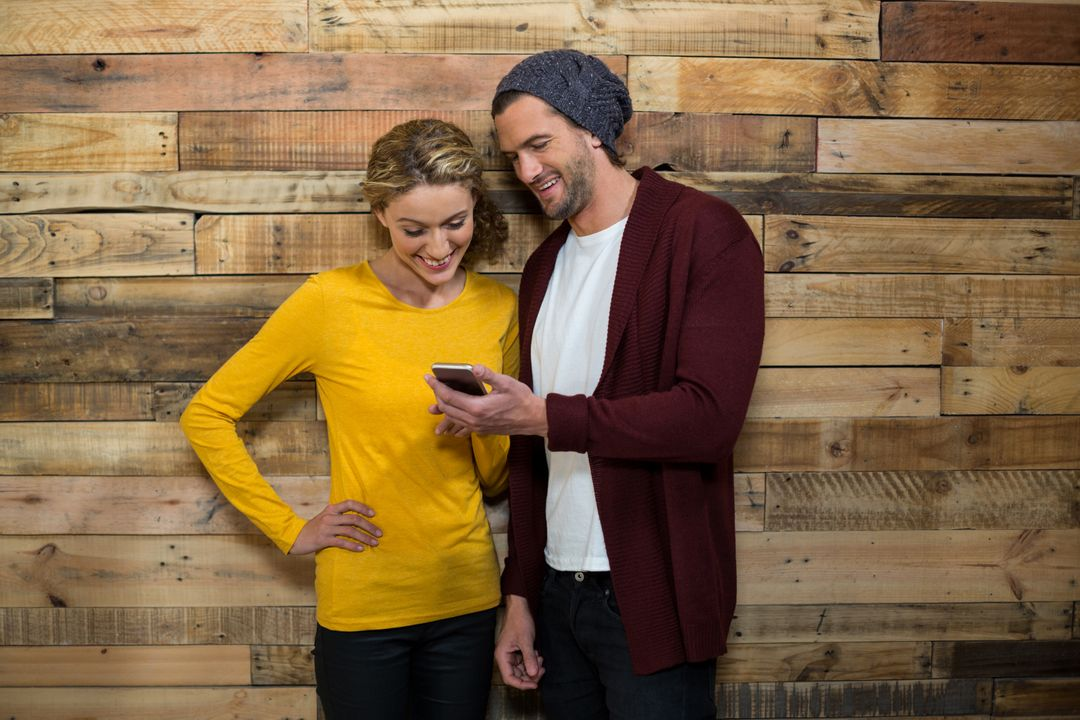Couple using mobile phone in café against wooden wall Free Stock Images from PikWizard