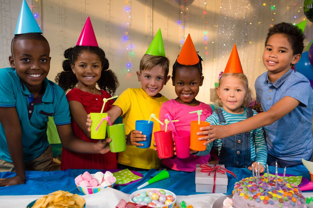 Portrait of smiling children toasting drinks while standing at table during birthday party Free Stock Images from PikWizard