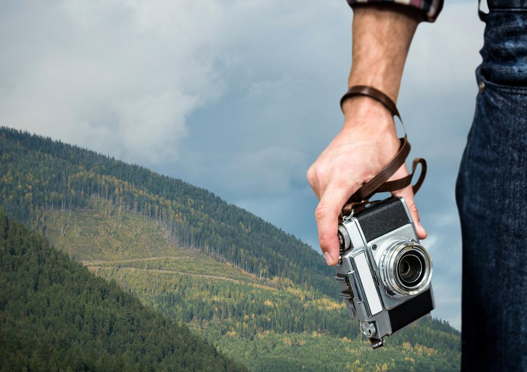 Digital composite of travel mountains. Hand with camera in fron of a green mountain Free Stock Images from PikWizard